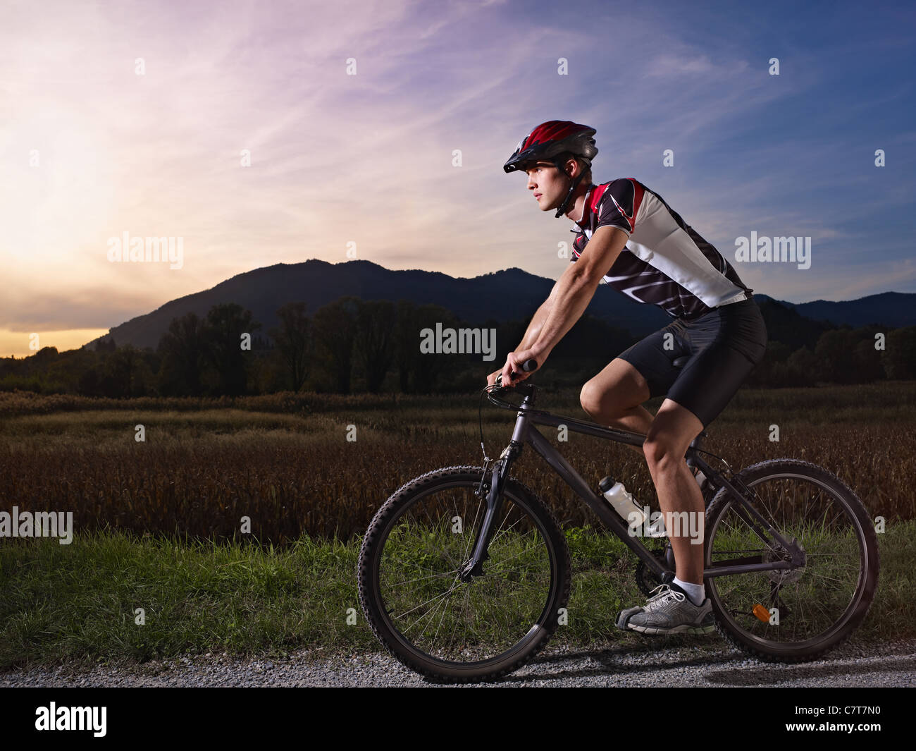 sports activity: young adult cyclist riding mountain bike in the countryside. Horizontal shape, side view, copy - Stock Image