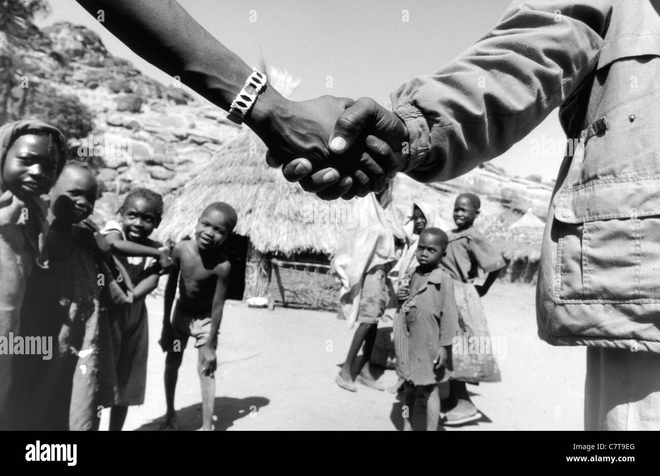 Sudan, Kordofan, hand shaking between soldier and locals - Stock Image