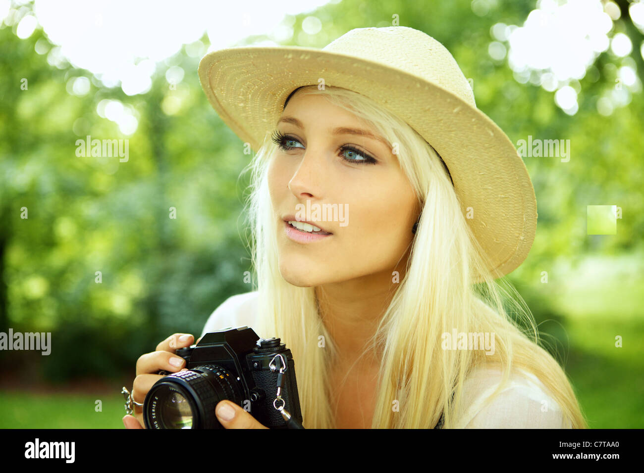 Girl with an old analog camera scouting for subjects.  - Stock Image
