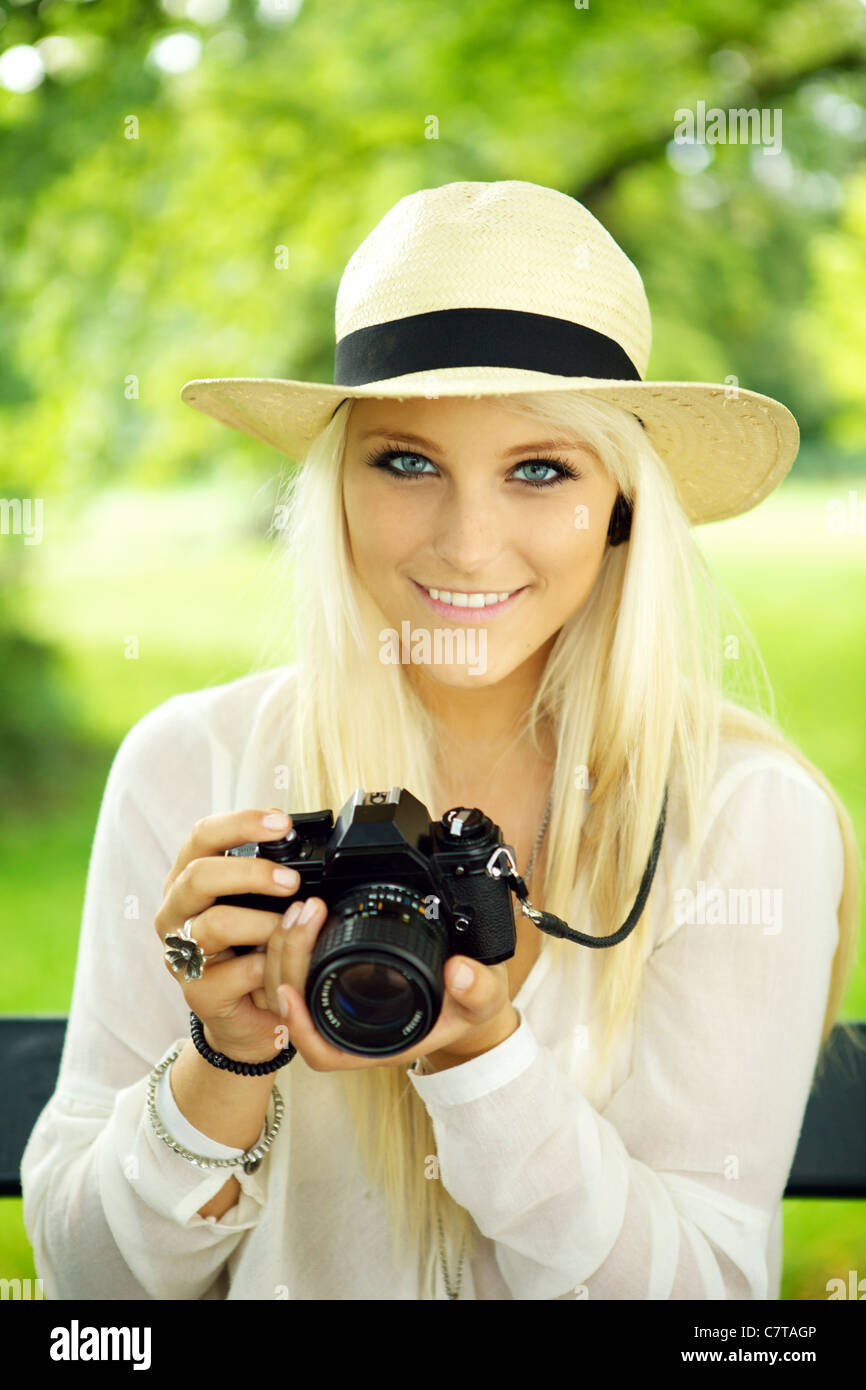 Portrait of a cute girl with an old-fashioned SLR camera.  - Stock Image