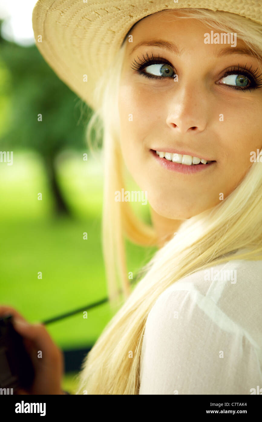 Close-up portrait of young woman with camera - Stock Image