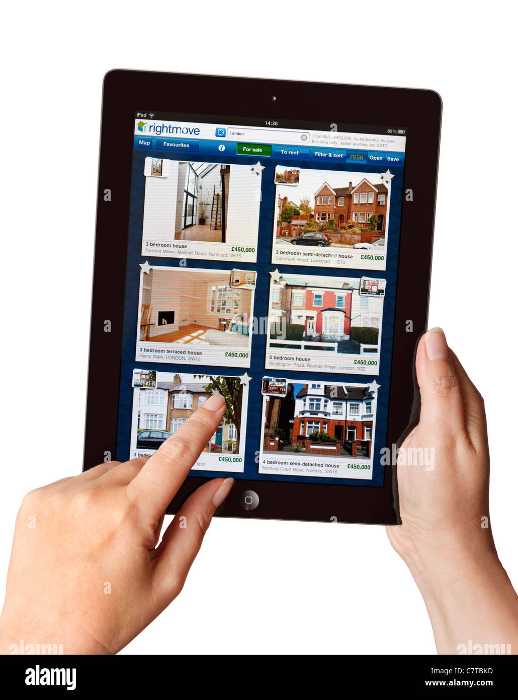 Hands holding iPad searching for a house for sale on the Rightmove app on a tablet - Stock Image