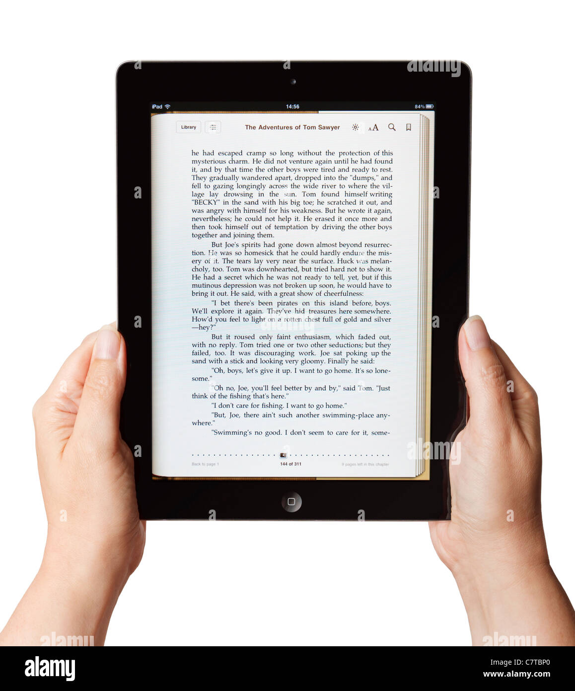 Female hands holding an iPad reading a book - Stock Image