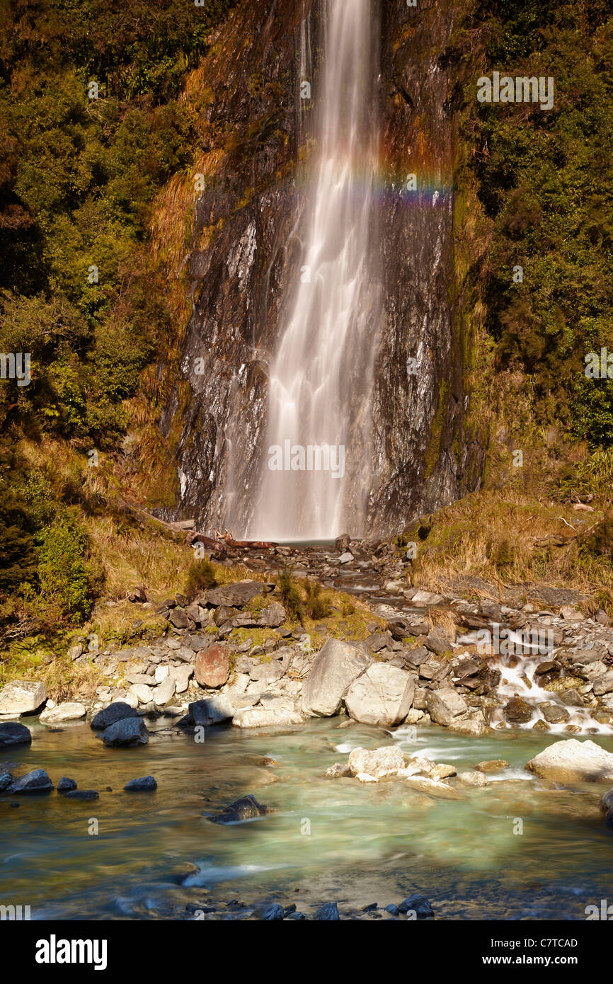 As the light hits Thunder Creek Falls it casts a rainbow over the cascades. - Stock Image
