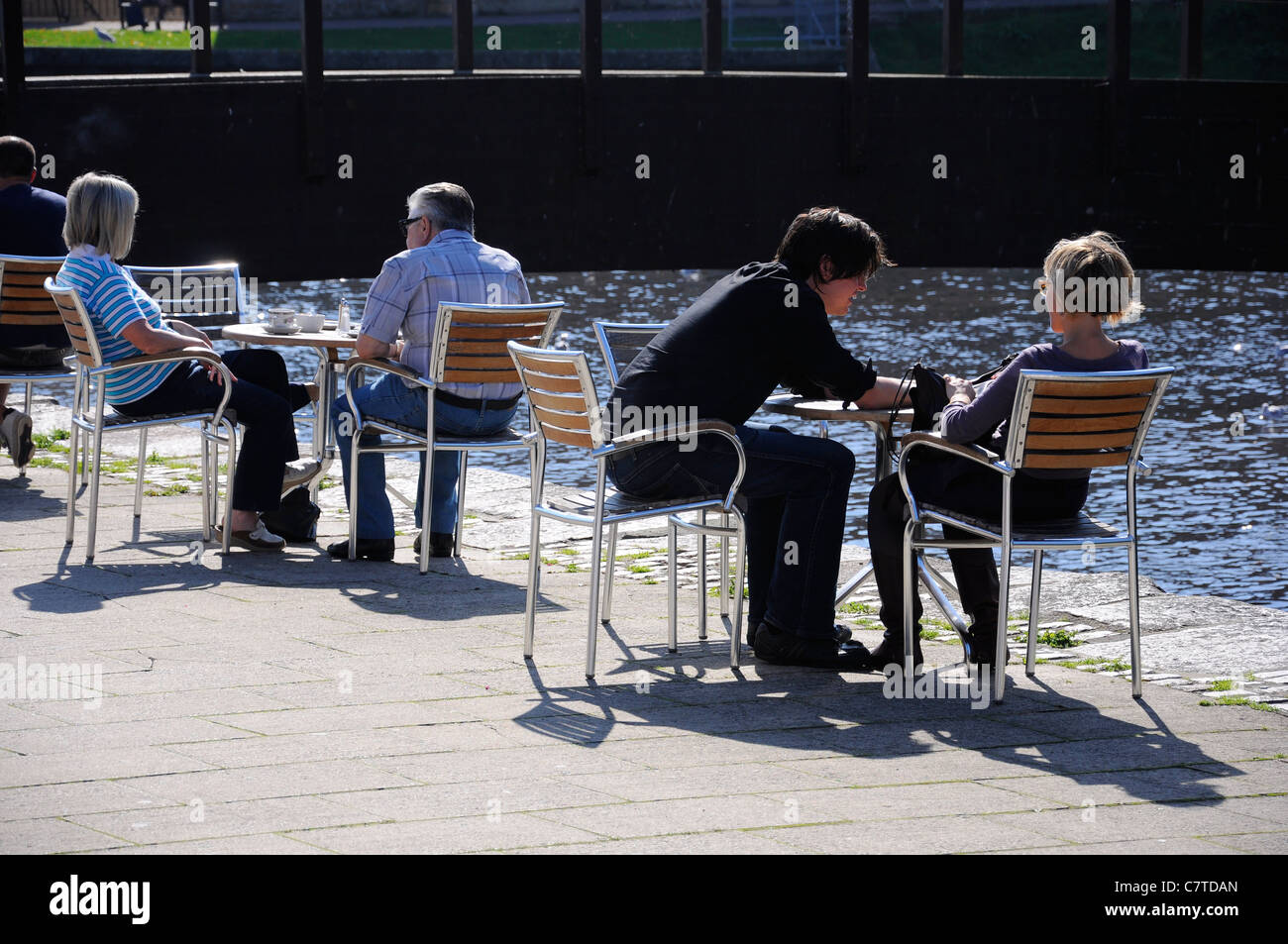 people sitting at outdoor cafe tables exeter quayside devon uk