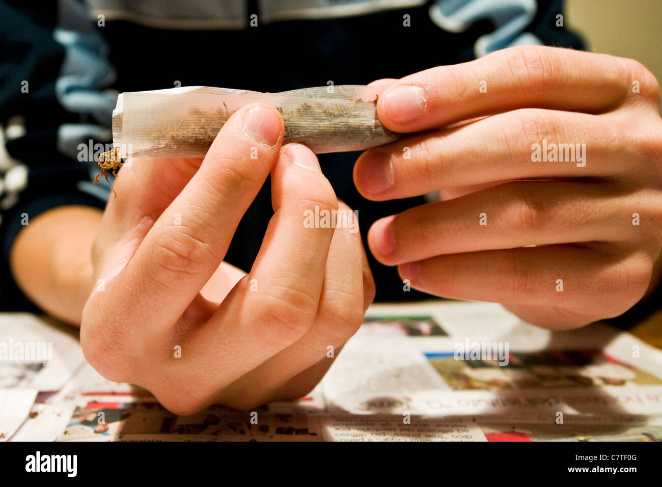 Young man's hands rolling marijuana joint, close up - Stock Image