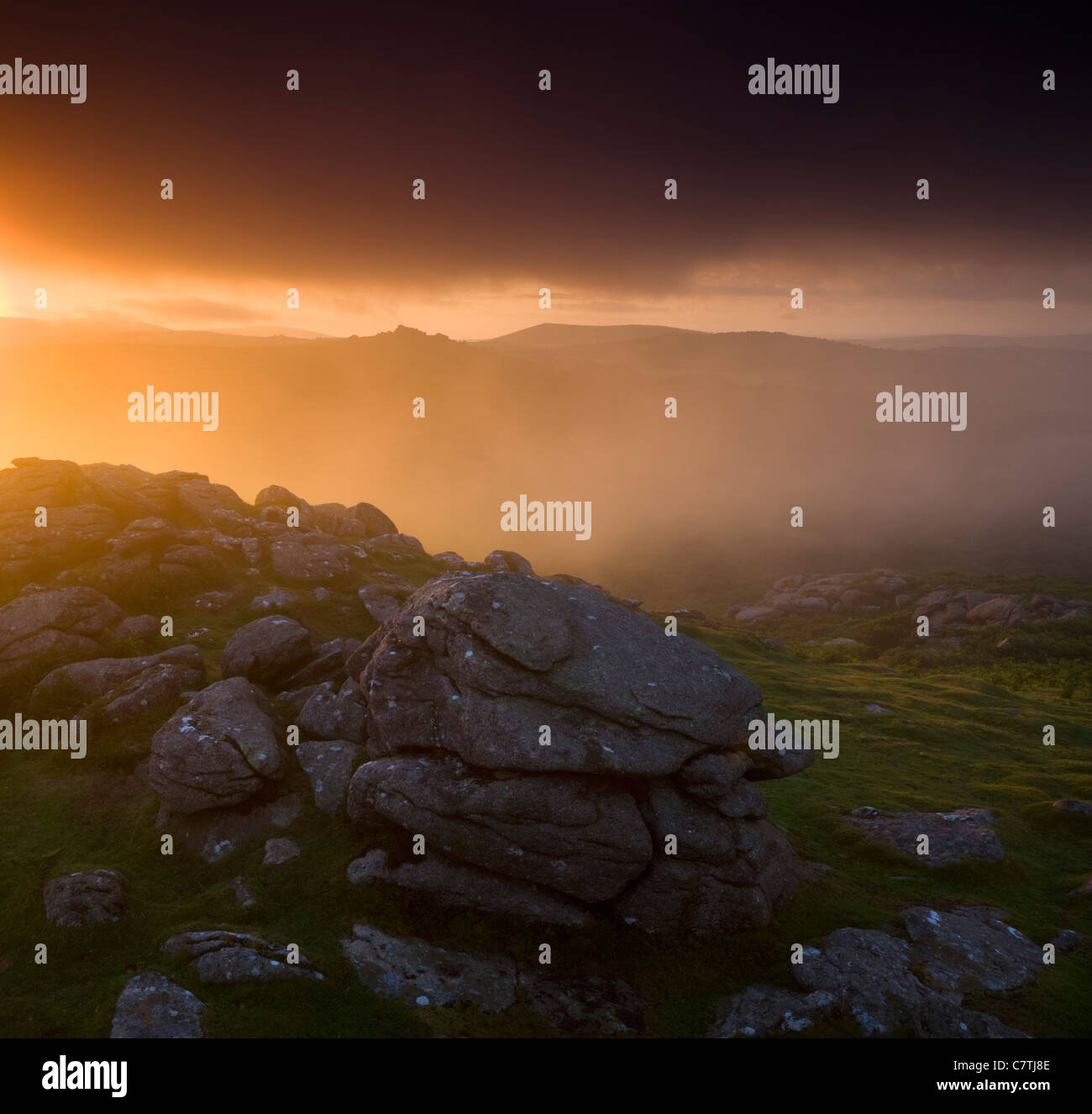 Views to Hound Tor from Holwell Tor on a misty sunset, Dartmoor, Devon, England. Summer (July) 2010. - Stock Image