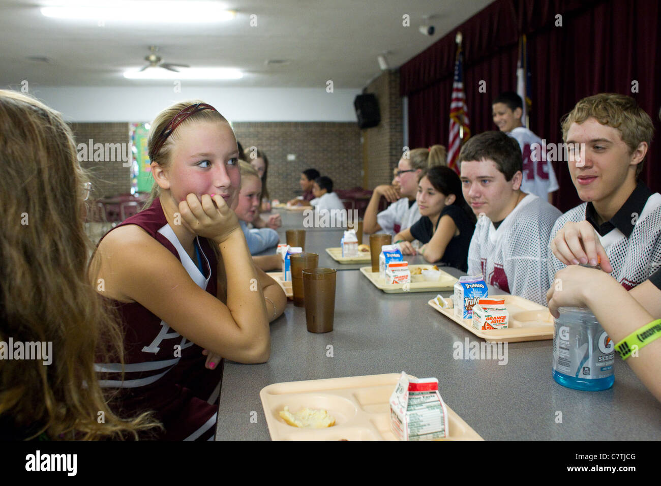Junior high students in the Paint Creek, TX schools sit and chat in the school's cafeteria for morning announcements. - Stock Image