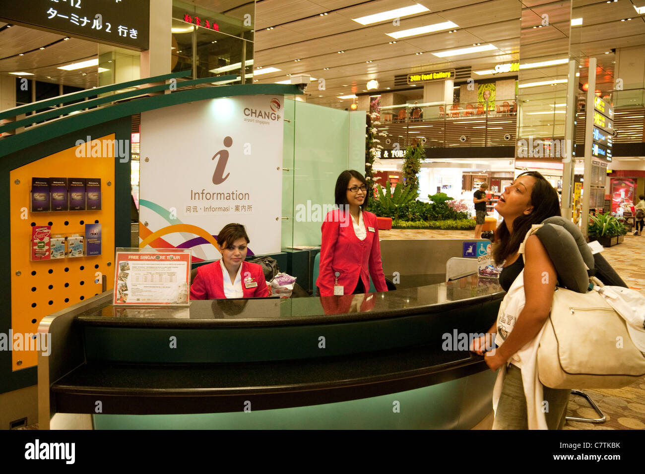 An air traveller at the Information desk, Changi airport singapore - Stock Image