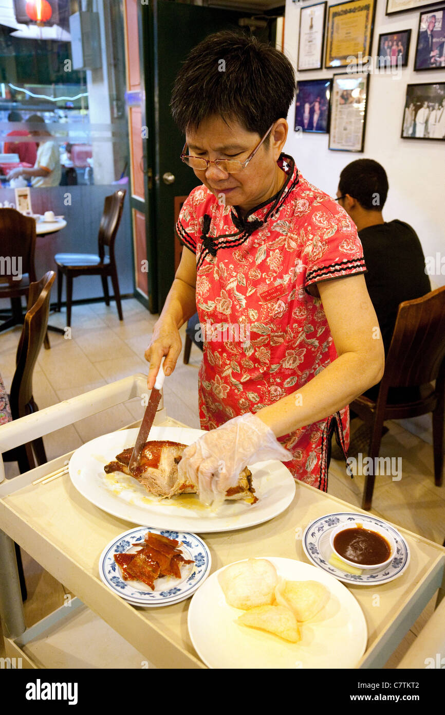 A waitress preparing Crispy duck in a Chinese restaurant, Chinatown, Singapore - Stock Image