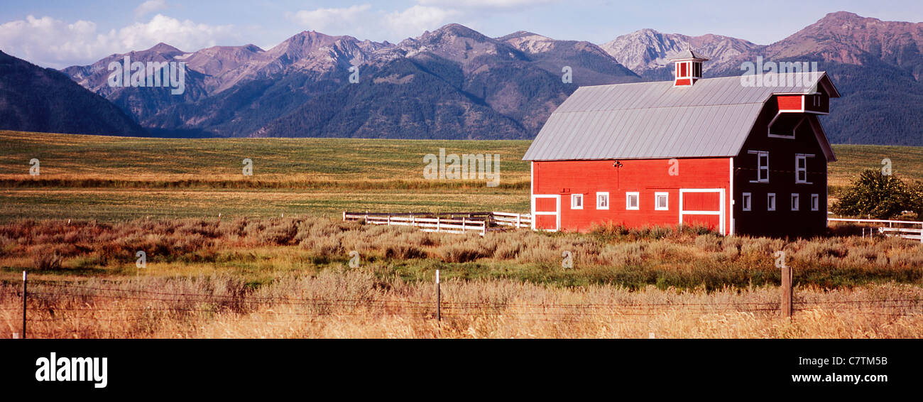 Red wooden barn in field and Wallowa Mountain range near Joseph in Eastern Oregon USA - Stock Image