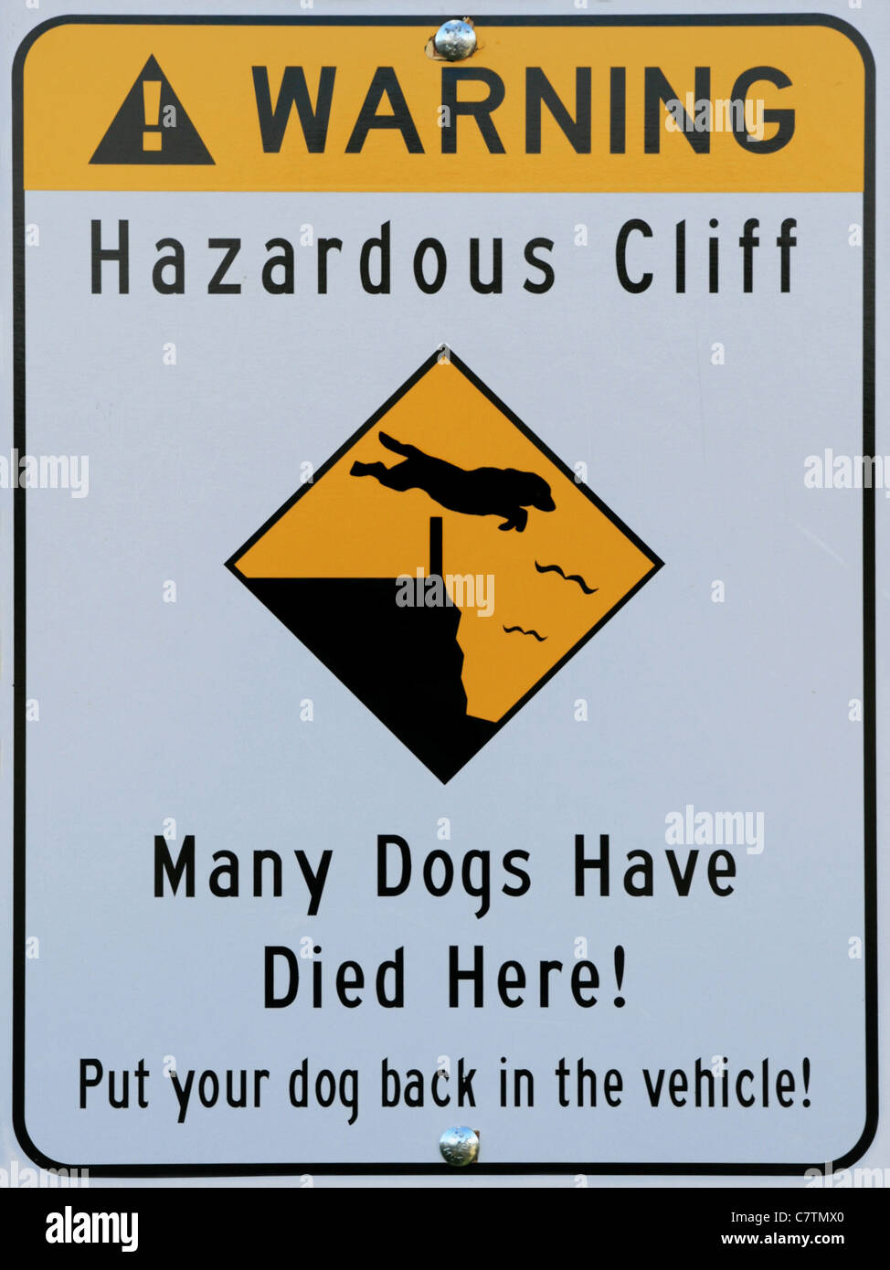 hazardous cliff warning sign showing a dog jumping over a fence and over a cliff - Stock Image