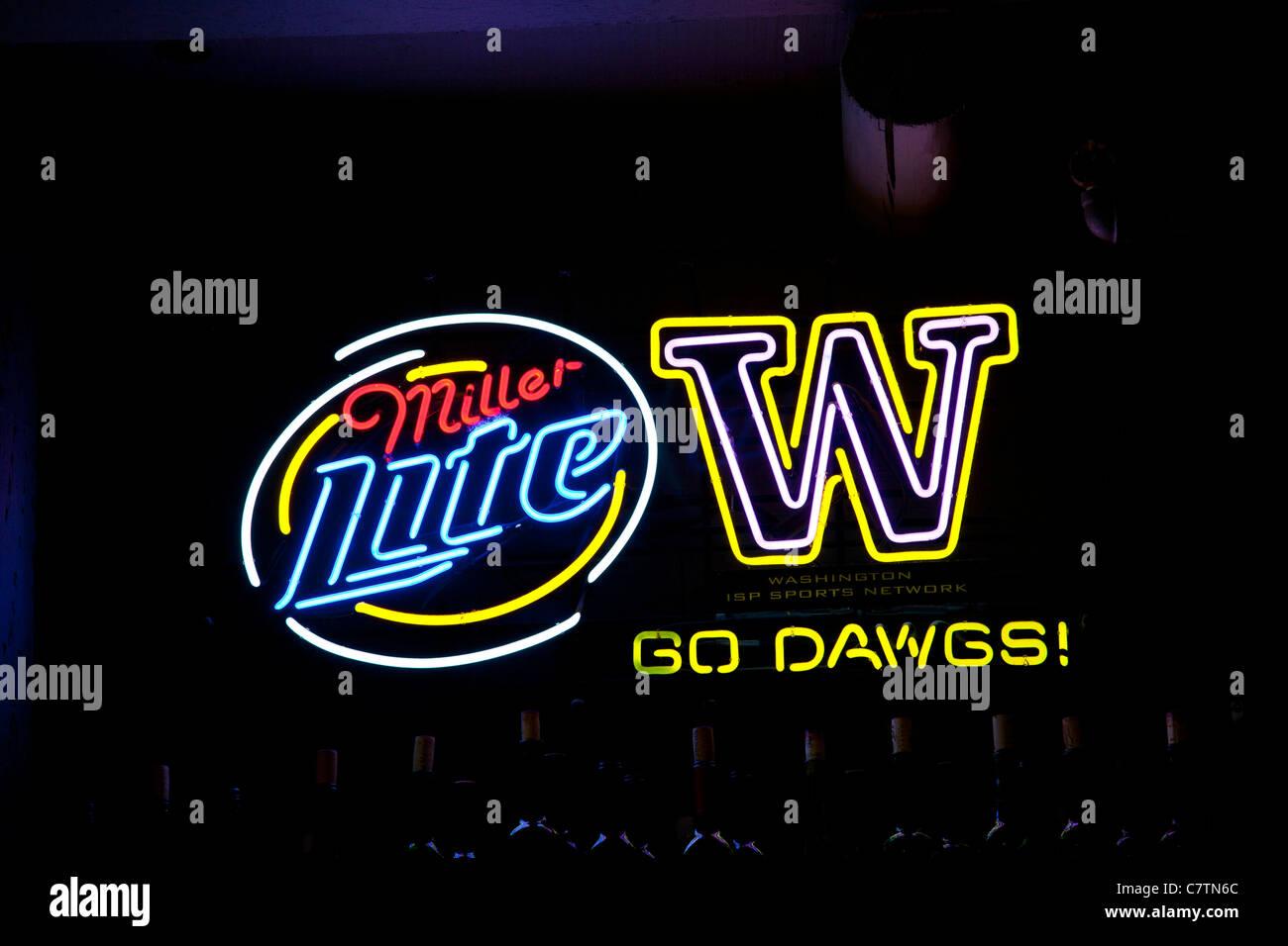 neon restaurant bar sign advertising Miller Lite beer with tie-in logo cheering University of Washington Huskies - Stock Image