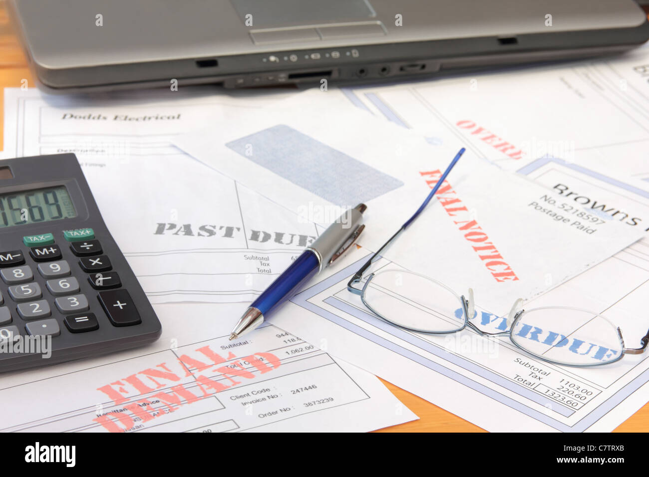 Overdue Bills with Calculator and Laptop Stock Photo