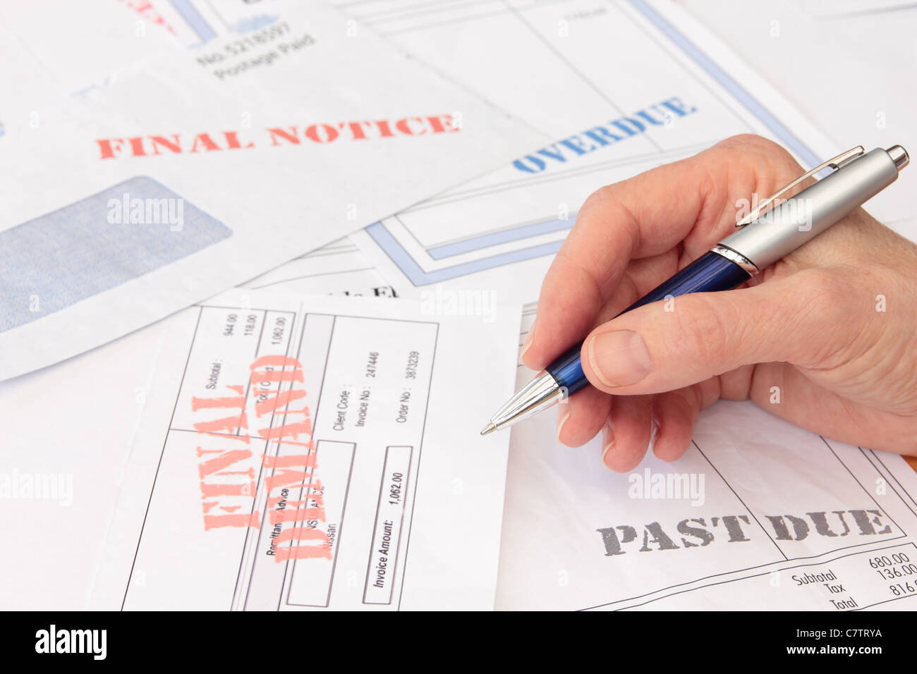 Overdue Bills and Invoices with Pen in Hand - Stock Image