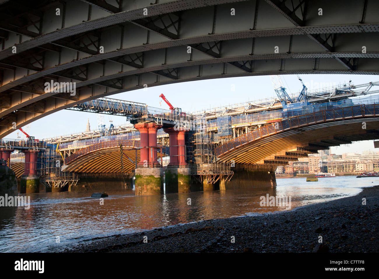 A view from below Blackfriars bridge London of the construction work being carried out on Blackfriars railway bridge. - Stock Image