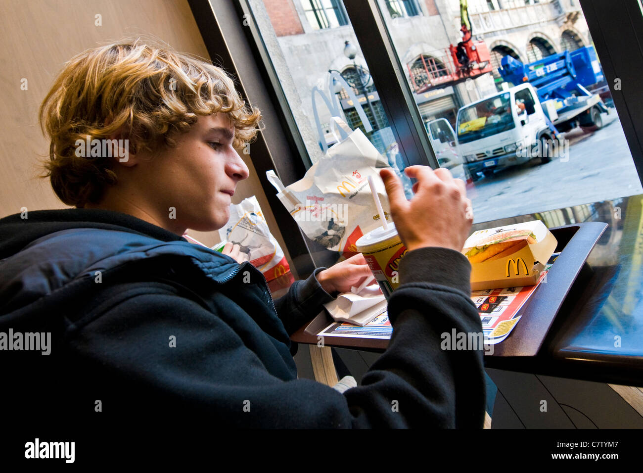 Teenage boy eating at fast food - Stock Image