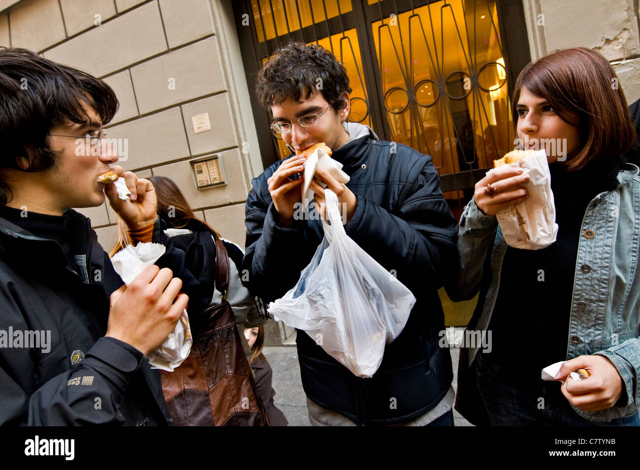Teenagers having a snack outdoors - Stock Image