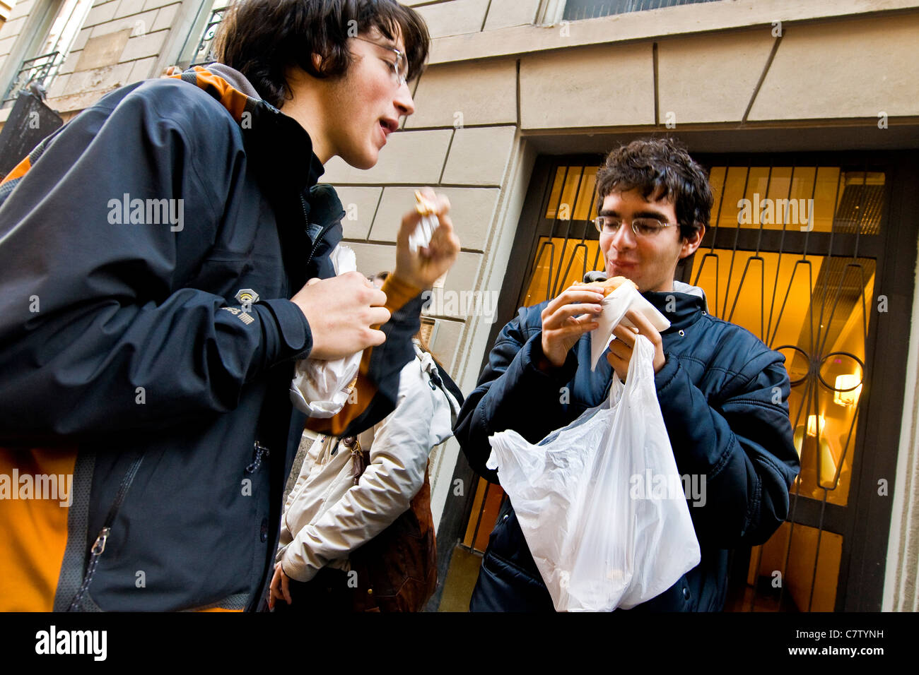 Teenage boys having a snack outdoors - Stock Image