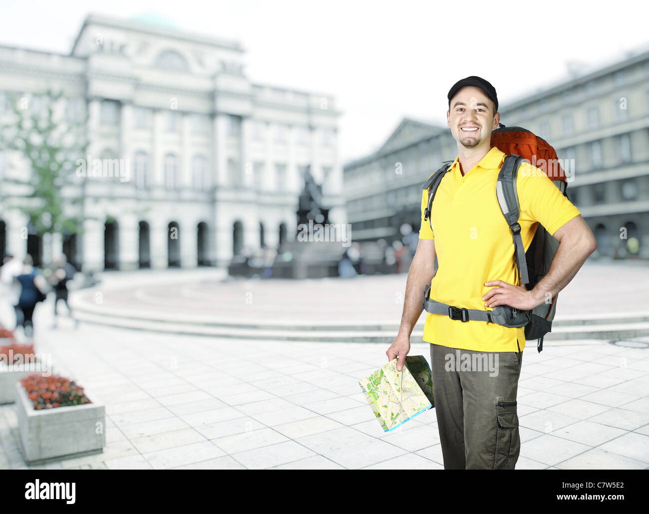 young traveller with map and town background - Stock Image