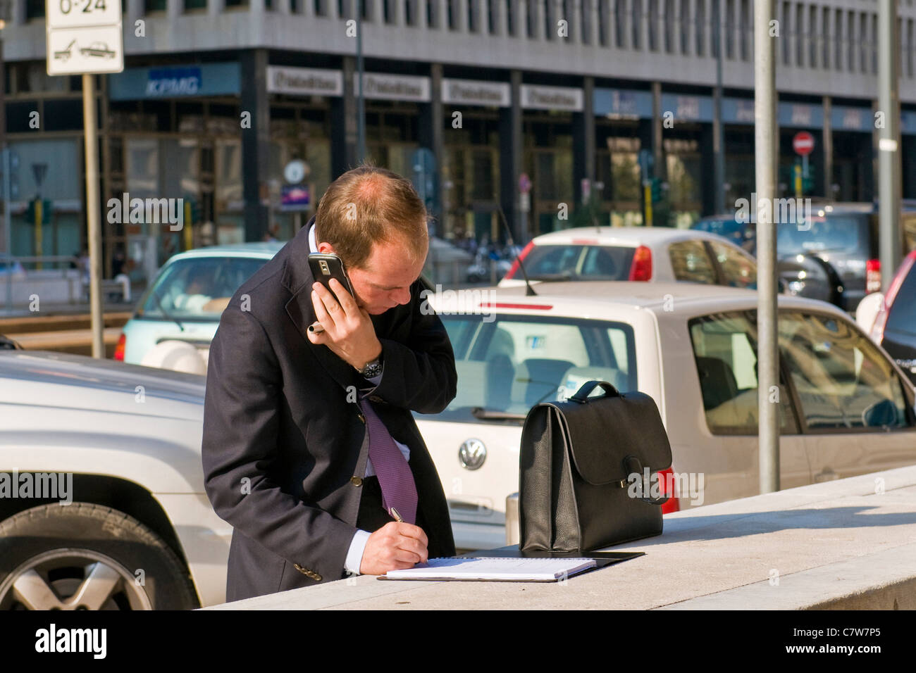 Businessman talking on mobile outdoors and writing on notebook - Stock Image