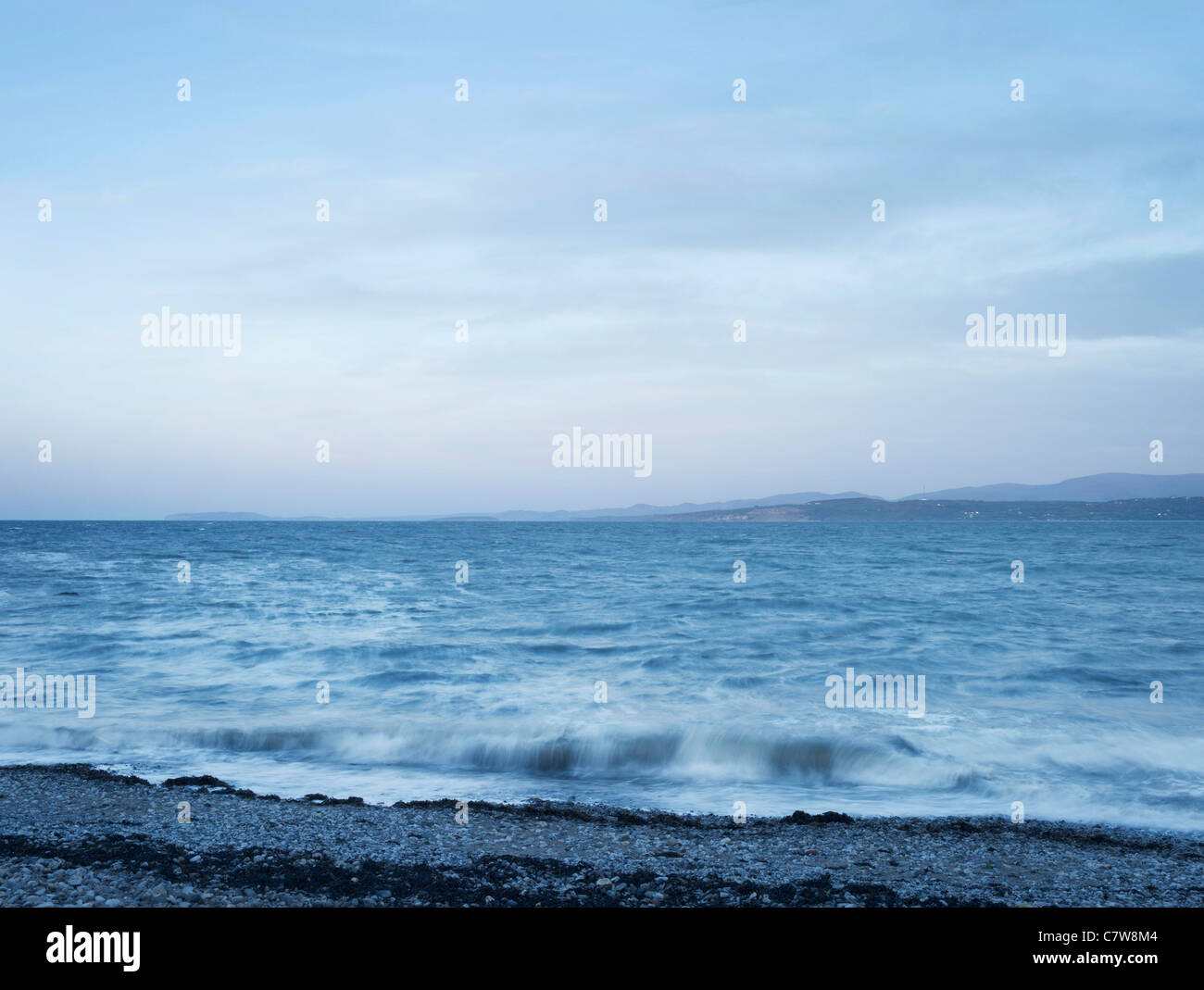 Anglesey seascape at dusk with pebble beach, with moving seas and sunset sky and mountains in the distance. - Stock Image