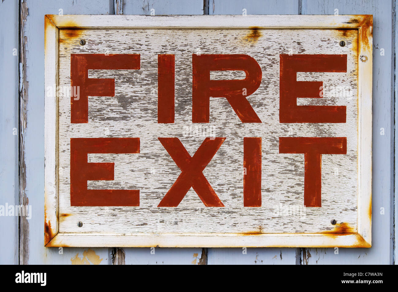 Photo of an old weathered FIRE EXIT sign on a blue door with peeling paint. - Stock Image