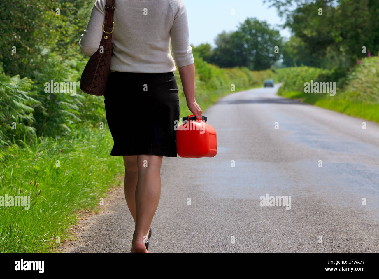Photo of a woman who's vehicle has broken down walking along a country lane with a spare fuel can in her hand. - Stock Image