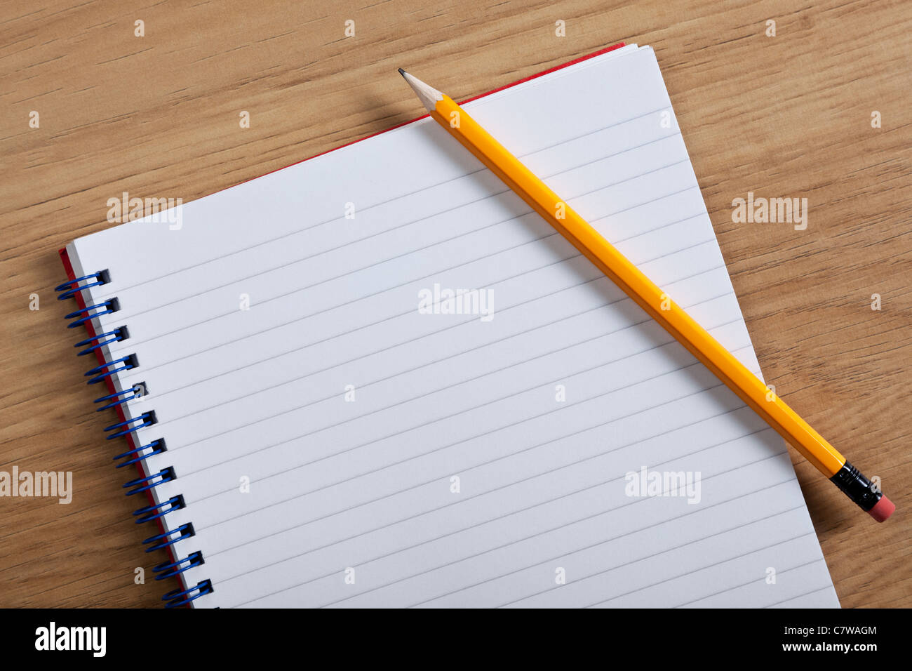 Photo of a blank ruled notepad and pencil on a desk, add your own copy. - Stock Image