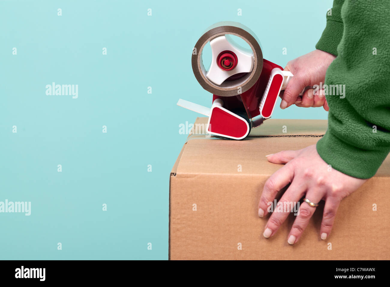 Photo of a womans hands taping up a cardboard box, can be used for removal or logistics related themes. - Stock Image
