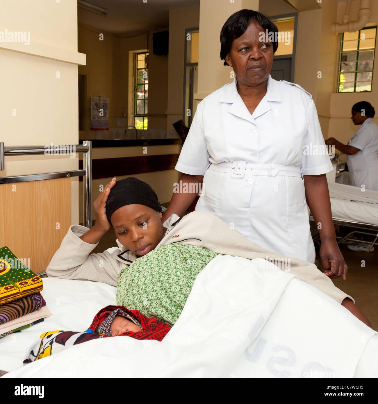 A maternity nurse with a mother and her two newborn twins, Marangu Hospital, Moshi, Tanzania - Stock Image