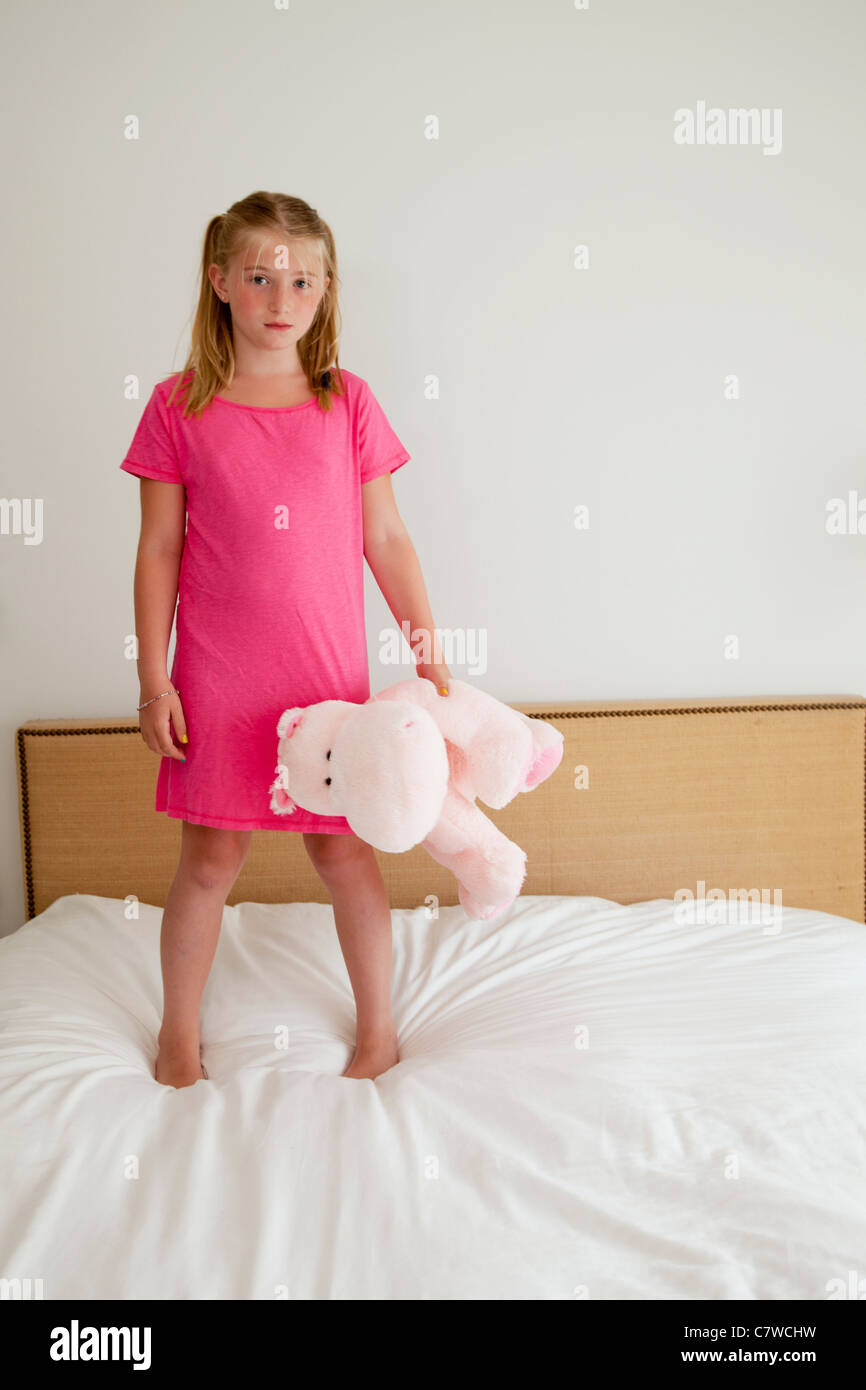 young girl on bed with stuffed animal - Stock Image