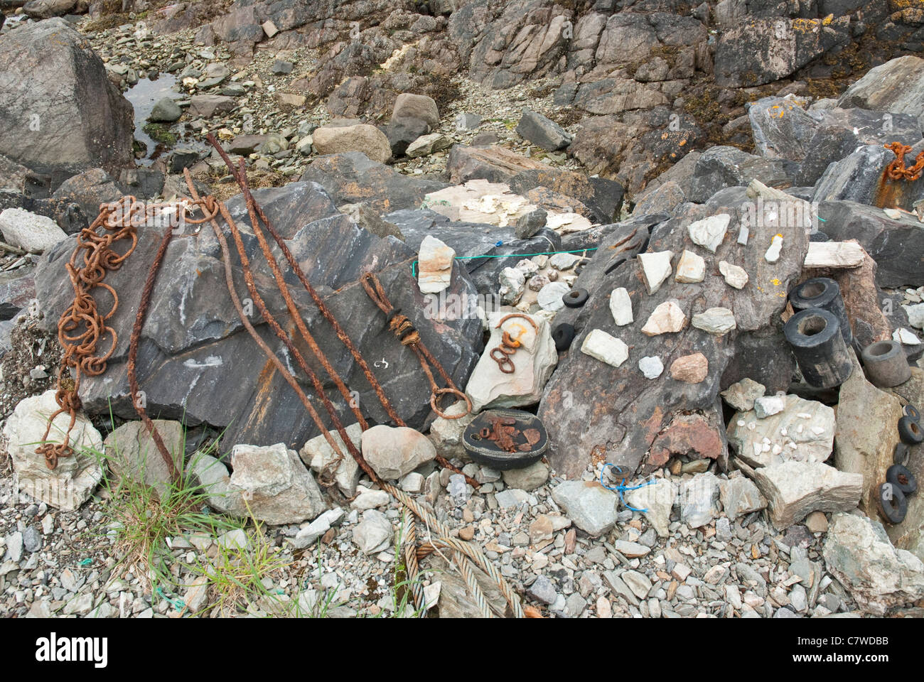 Beachcombing, small found items and stones arranged on rocks - Stock Image