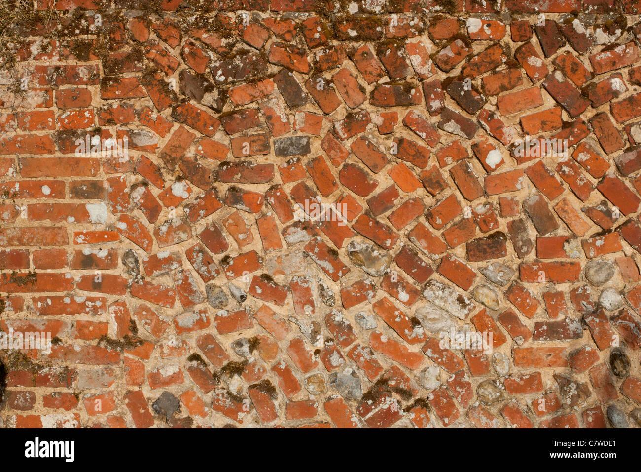 Red brick wall with bricks at odd angles - Stock Image