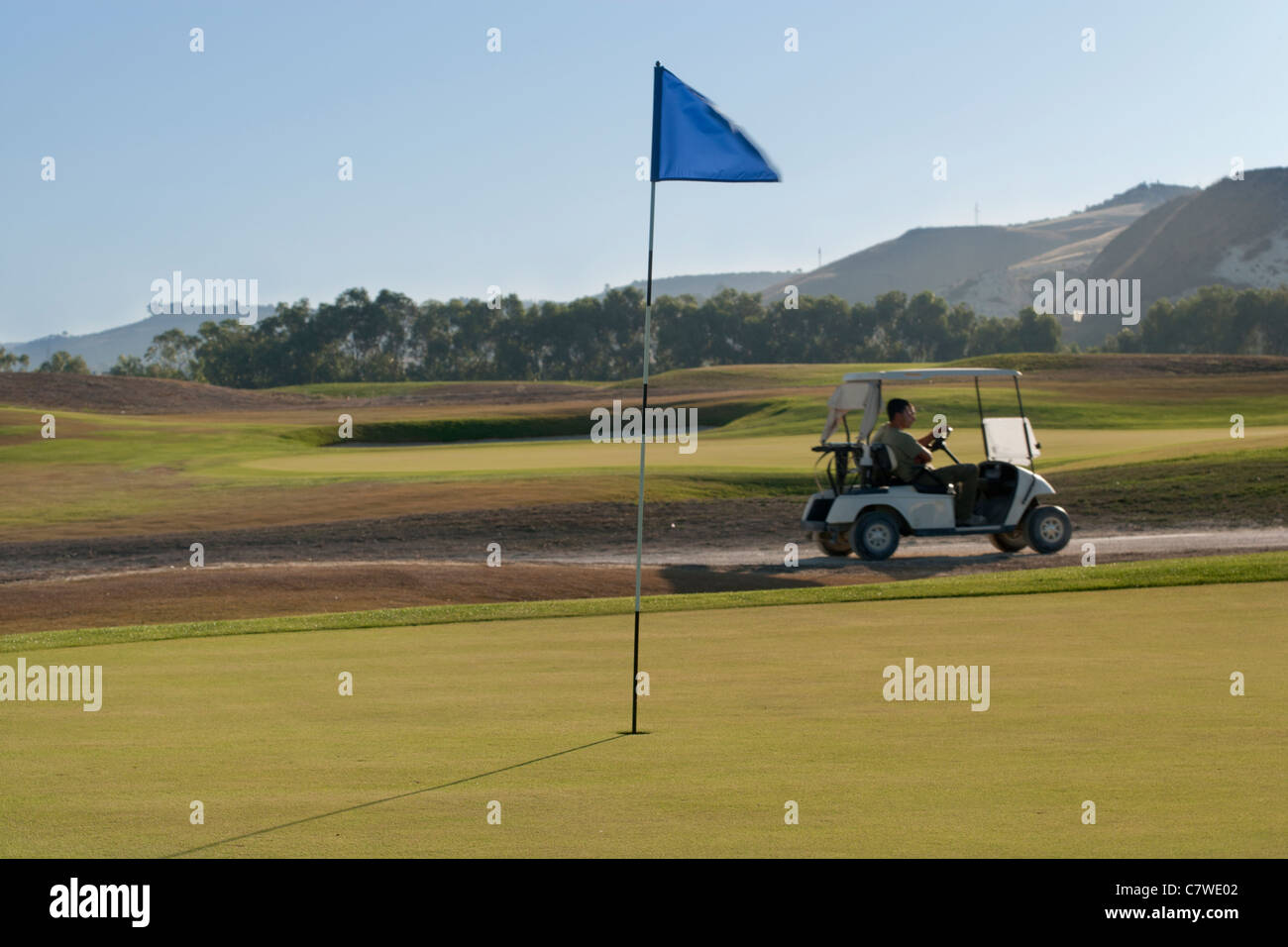 Golf buggy passing a golf green with a blue flag - Stock Image