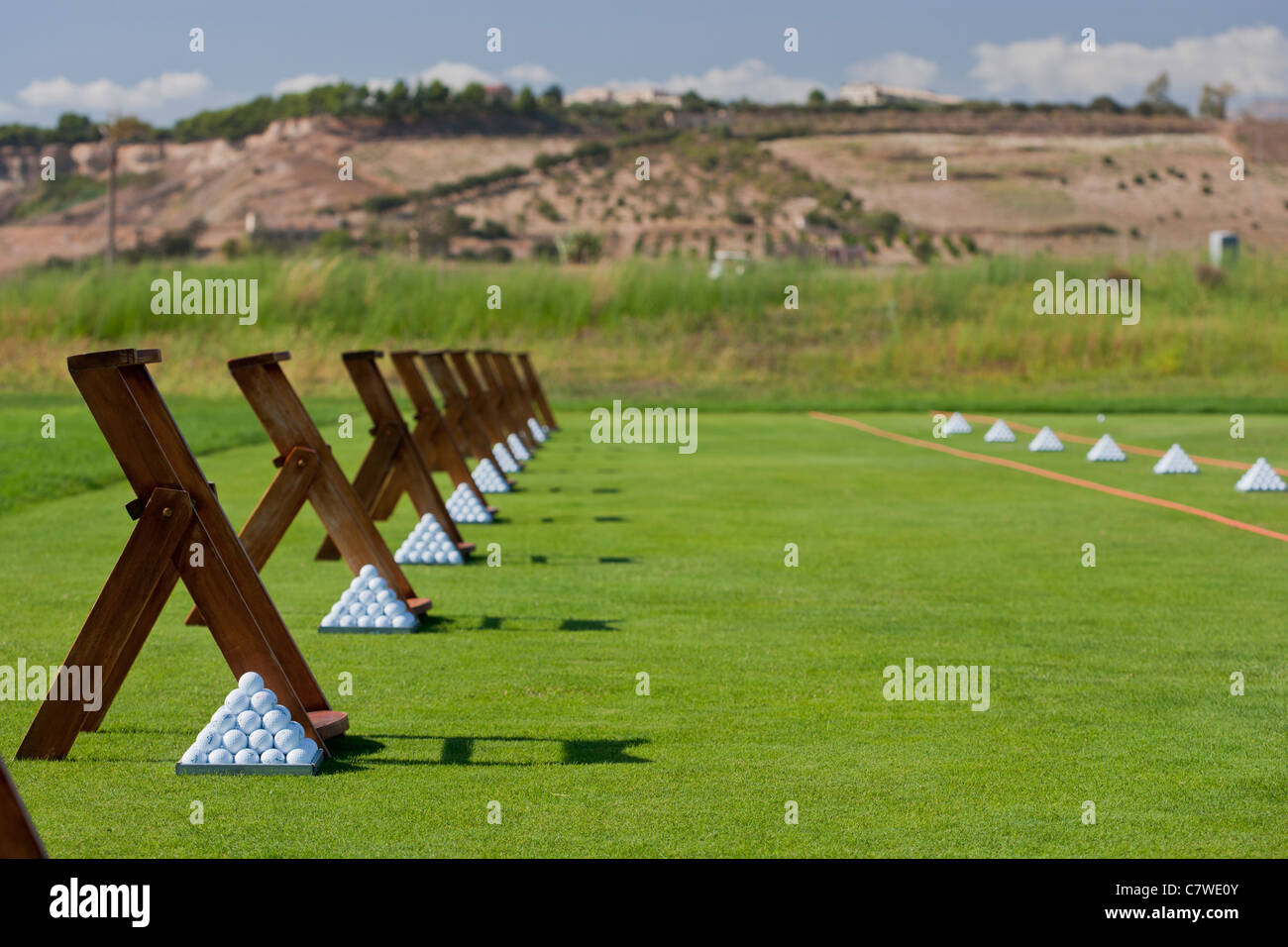 Pyramids of golf balls at a Golf driving practice range Stock Photo
