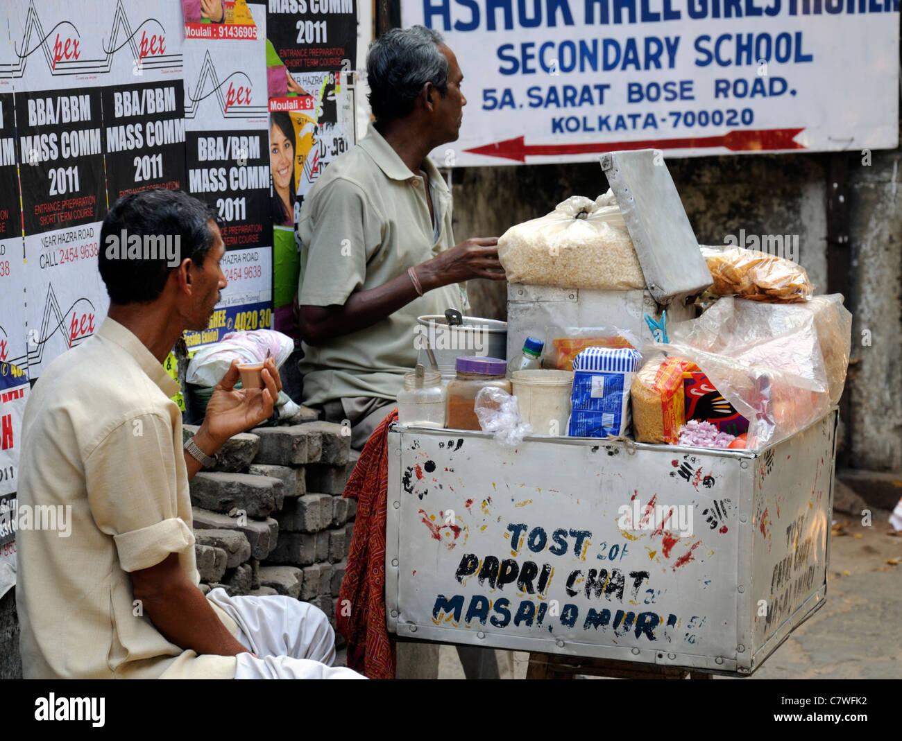 two men drink drinking enjoy enjoying tea chai food stall street stand kolkata calcutta west bengal india - Stock Image