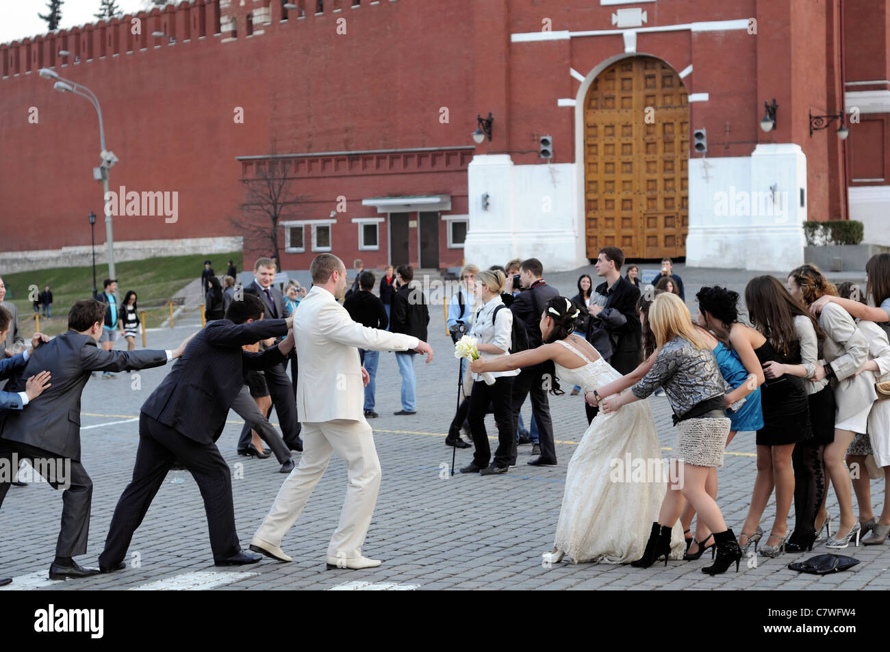 bride groom bridal party game pretend pretending to pull apart back from each other red square moscow russia separate - Stock Image