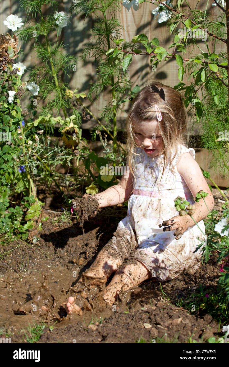 f9bbbef3210 young girl wearing pretty sat in muddy puddle splashing around - Stock Image