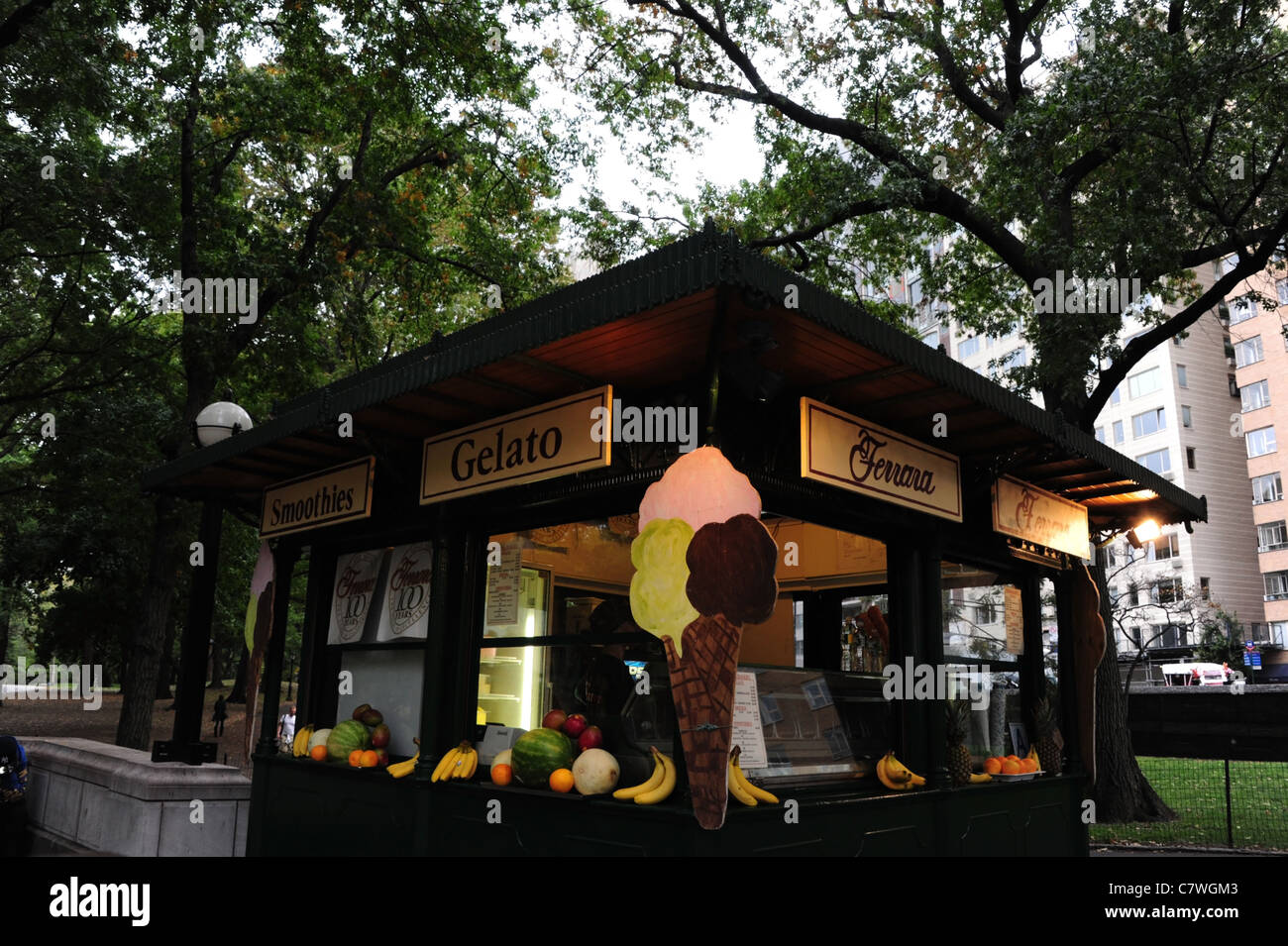 Ferra Cafe ice cream kiosk, with wall corner 3 scoop cone cut-out, below trees, Merchants' Gate Plaza, Central - Stock Image