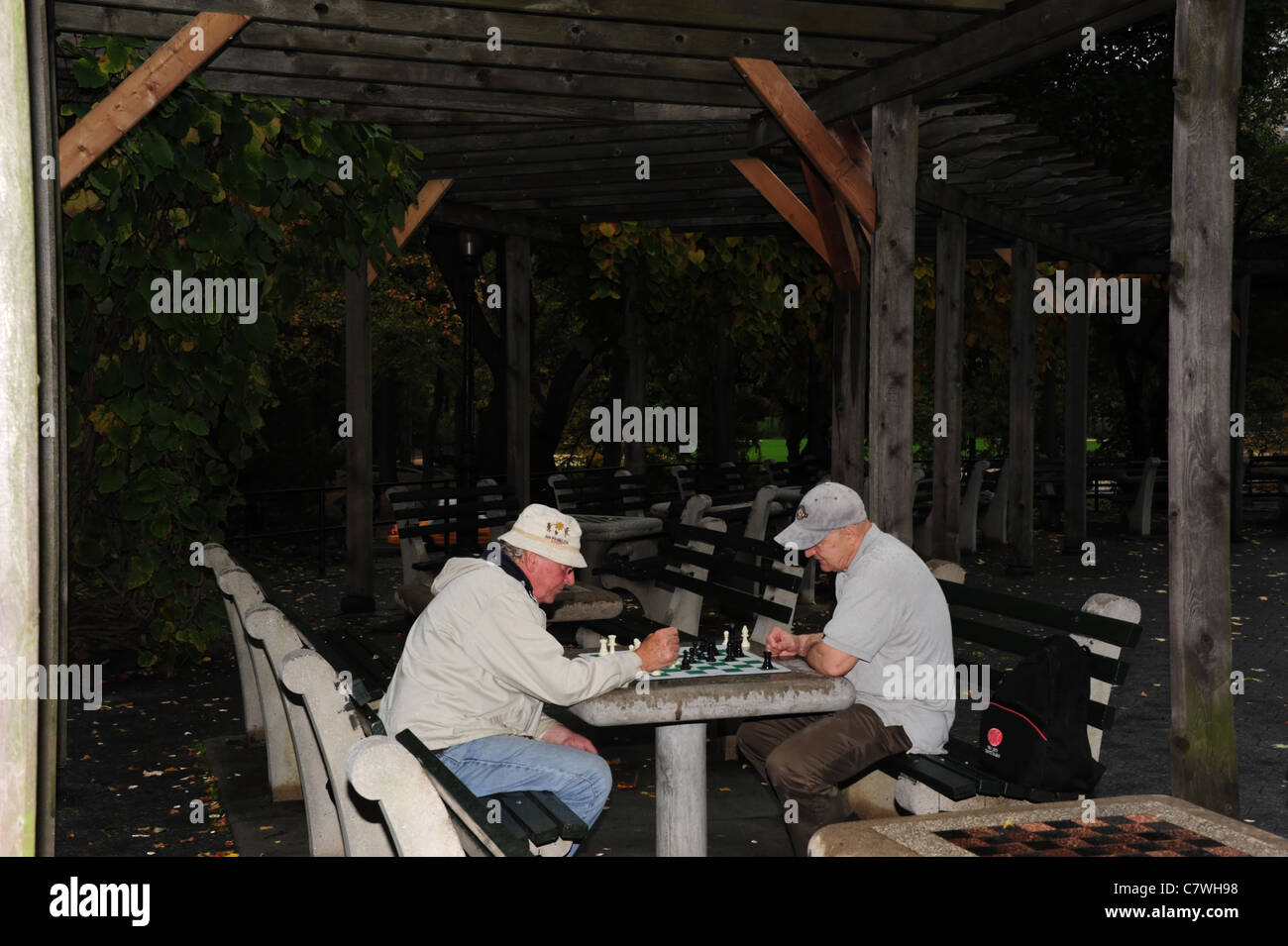 Two elderly men playing chess on a concrete table under a rustic pergola, Chess and Checkers House, Central Park, - Stock Image