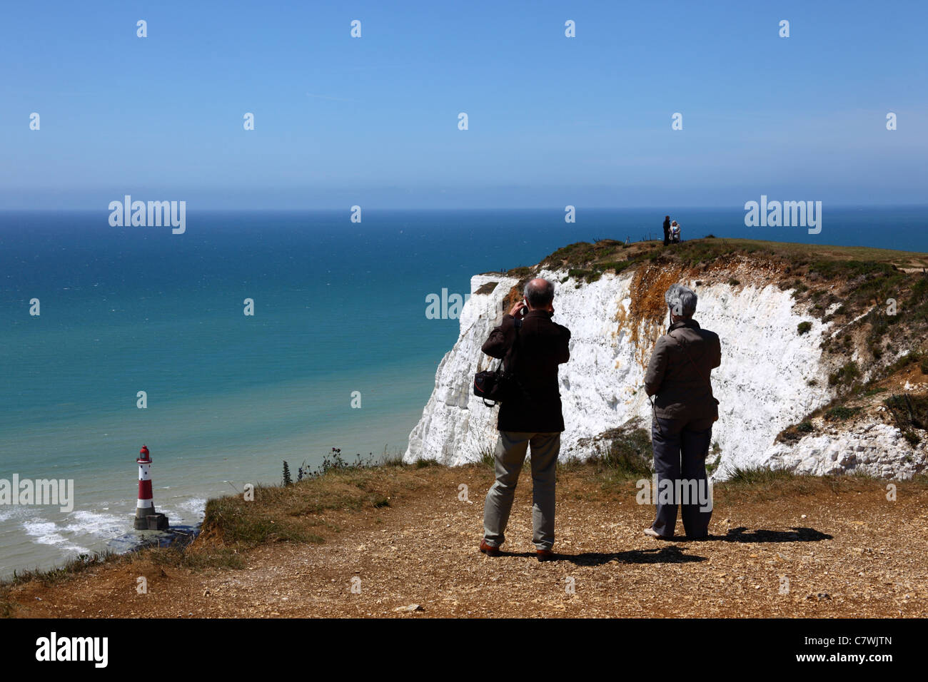 Tourists looking at view at Beachy Head , lighthouse in background , near Eastbourne , East Sussex , England Stock Photo