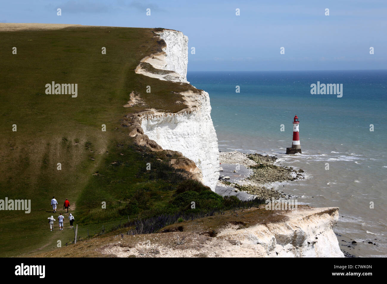 Hikers walking along South Downs Way coast path, Beachy Head lighthouse in background , near Eastbourne, East Sussex Stock Photo