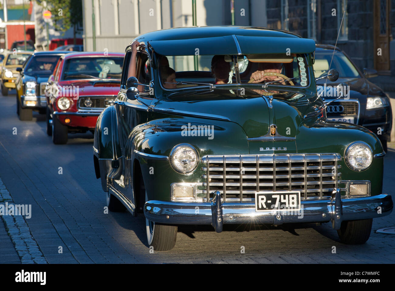 Dodge and other vintage cars driving through central Reykjavik, the capital of Iceland. - Stock Image
