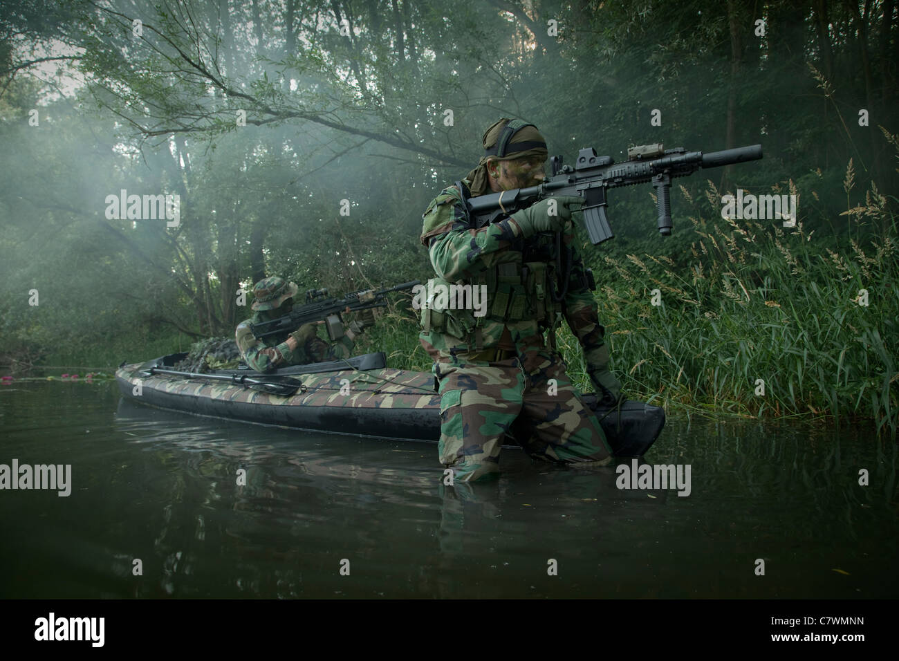 Navy SEALs navigate the waters in a folding kayak during jungle warfare operations. Stock Photo