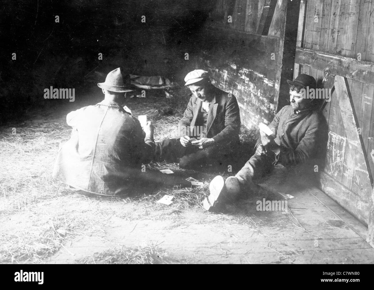 Tramps play cards in box car, USA - Stock Image