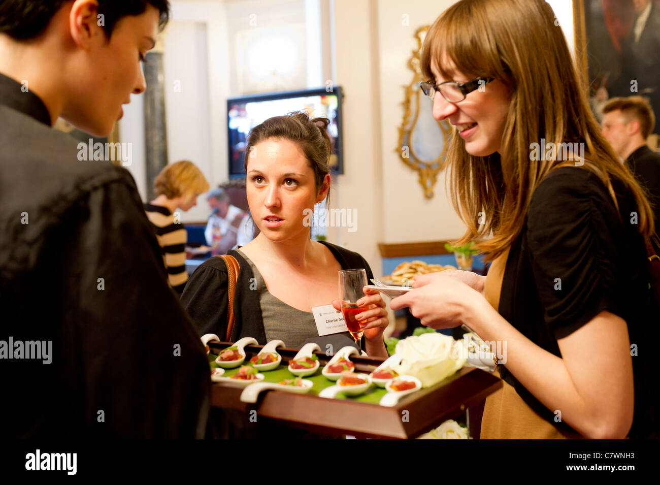 Female guests sampling canapes at corporate event in London - Stock Image