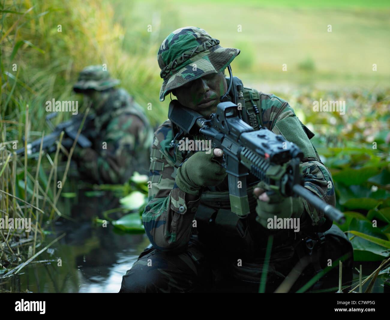 U S  Navy SEALs cross through a stream during combat