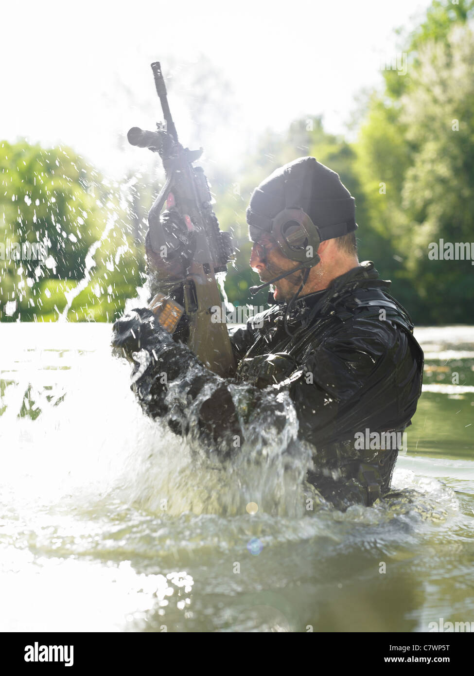 Special operations forces soldier emerges from water armed with a Steyr AUG assault rifle. - Stock Image