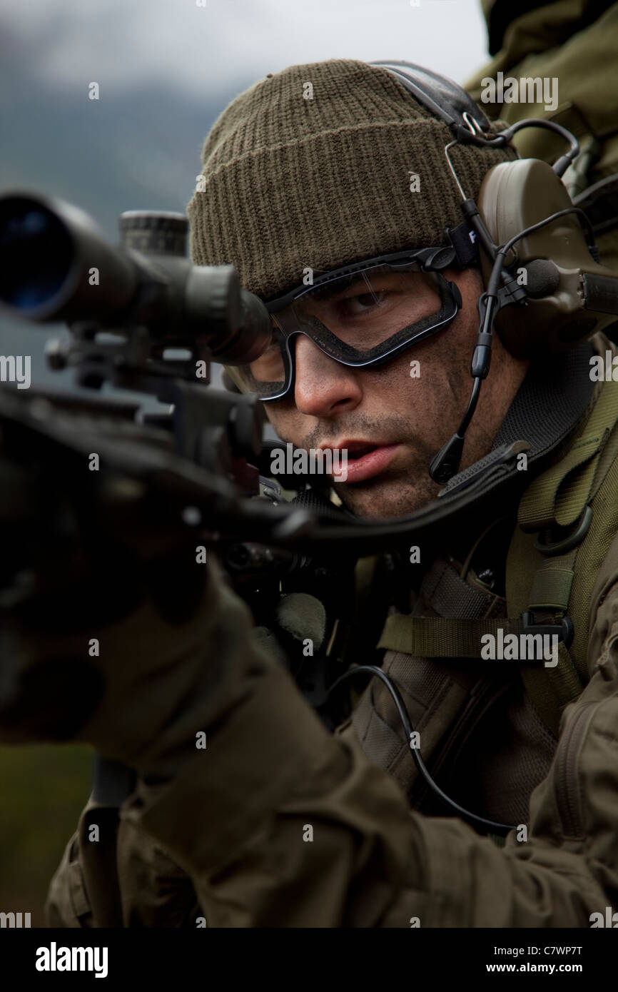 U.S. special forces soldier stays alert while armed with an automatic rifle. - Stock Image